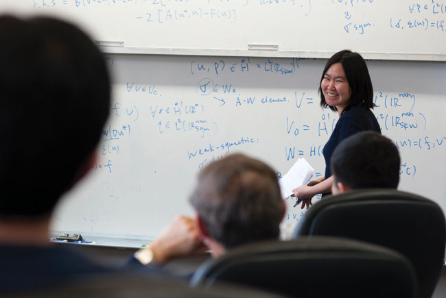 Professor giving lecture in front of white boards with covered with equations