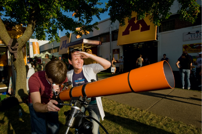 young man and woman looking through large orange telescope in front of U of M building at Minnesota State Fair