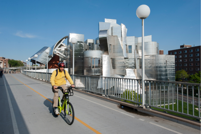 Student riding a NiceRide bicycle across pedestrian bridge with Weisman museum in background