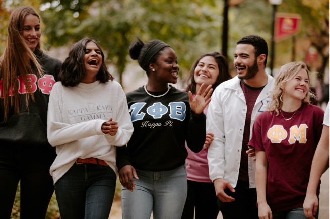 Students of different races and ethnicities wearing sweatshirts from various sororities and fraternities on campus