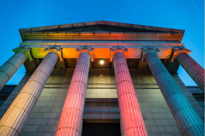 Ionic columns of Minneapolis Institute of Arts lit from below in rainbow colors with dark night sky behind