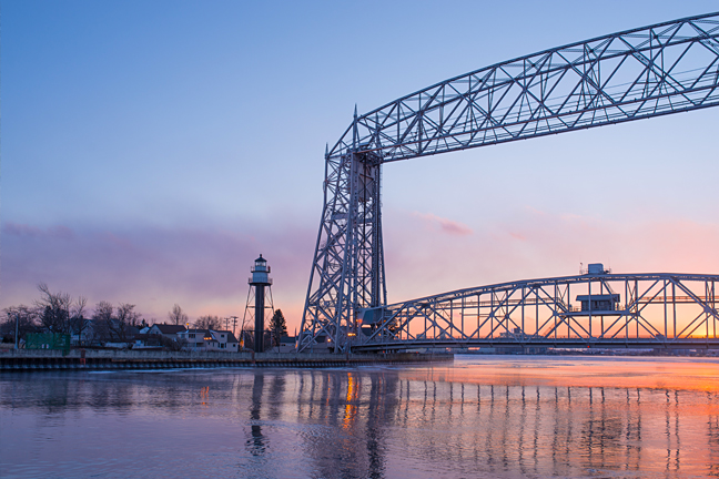 Photo of sunset reflected in Lake Superior. Visible across the water is a lighthouse and the Aerial Lift Bridge—landmarks of Duluth, Minnesota.