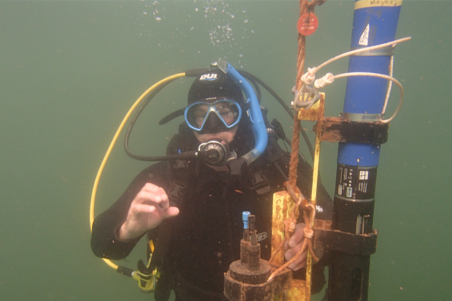 Photo of diver collecting data at a buoy in Lake Superior.