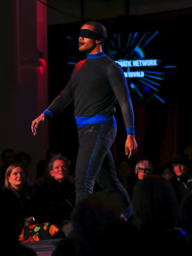 Male model on runway wearing black top and pants with blue horizontal hoop at waist and cuffs, and black cloth over eyes