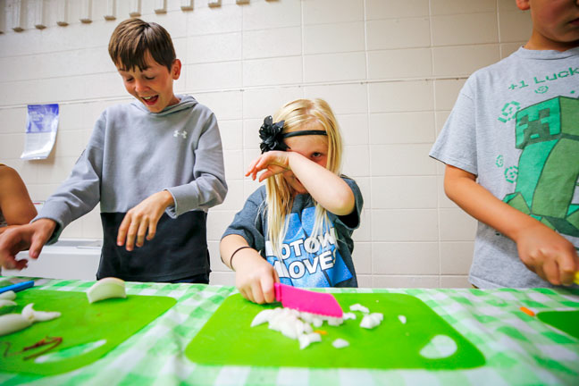 Closer view of girl cutting onions and wiping her eyes from the onion reaction