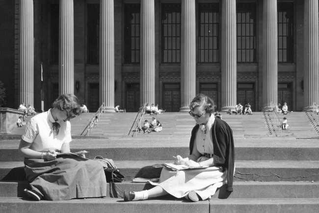 black and white image of two female student studying on steps in front of Northrop, appearing to be from the 1940s