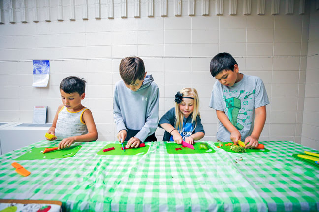 four kids chopping vegetables at a market event