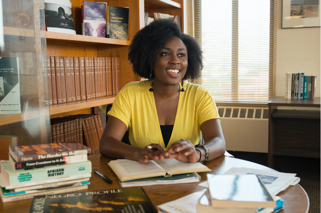 African-American female student working at desk in college office