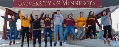 students in U of M sweatshirts on pedestrian bridge over Mississippi