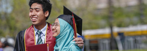 Male Asian student wearing graduation gown and tie and female student wearing graduation cap and head covering smile after graduation ceremony