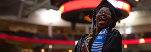 black female student with cap and gown celebrates graduation