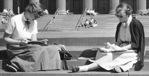 black and white image of two young female students studying on the plaza with Northrop visible in background