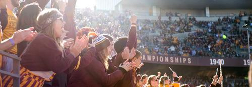 students cheering the Gopher football team from the student section of TCF Bank stadium