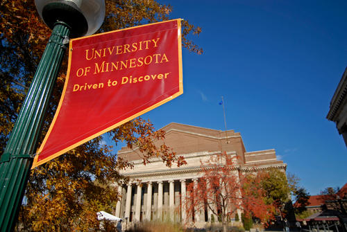 A Maroon banner with Gold text reading University of Minnesota, Driven to Discover hangs off a light post in the foreground, with Northrop's facade in the background on a clear, autumn day