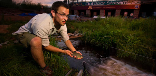 researcher hold small fish at the stream lab