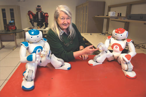 Maria Gini with two robots in her lab