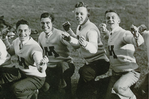 Male students wearing M sweaters and posing on field