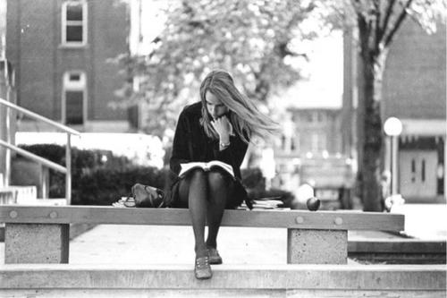 Young woman studying on stone bench on campus