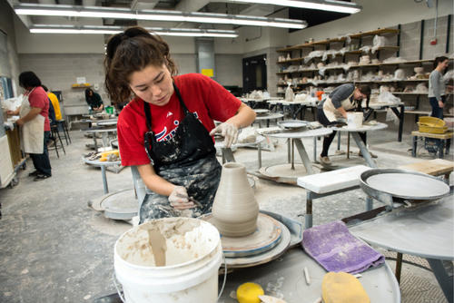 Student working on clay wheel in ceramics class