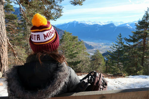 student wearing U of M winter hat looking out at mountain scene