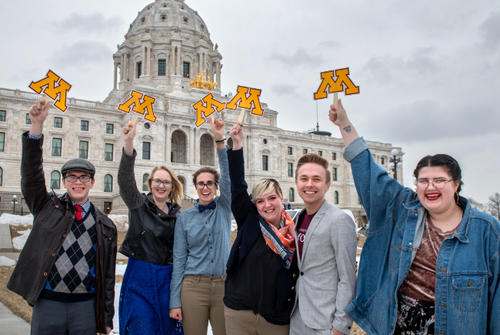 Group of people holding U of M block M logo at the State Capitol
