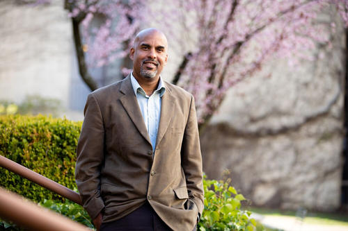 Damien Fair, bald, bearded and Black, wears a brown suit jacket and stands before a flowering tree.