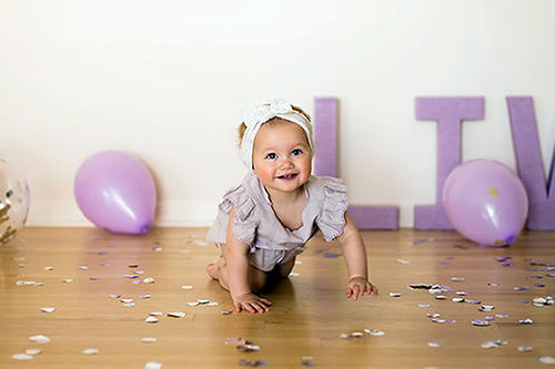 Baby Livi, white, crawls on a wooden floor with purple balloons.