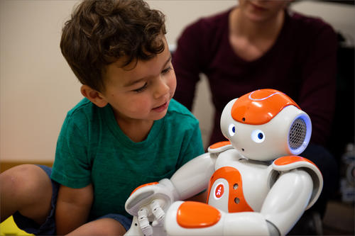 toddler inspects robot with look of awe and curiosity