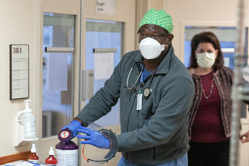A man and a woman, both wearing masks, in a health care setting.