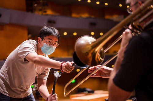 Mechanical engineering Ph.D. student Ruichen He uses an aerodynamic particle sizer to measure aerosol concentration near the outlet of a trombone played by Minnesota Orchestra Principal Trombone R. Douglas Wright.