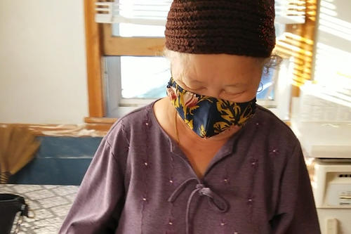 A Hmong elder, dressed i purple with a knit cap and mask, looks down.