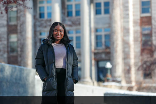 Gbemi Oyetunde wearing long winter coat with columned building in background