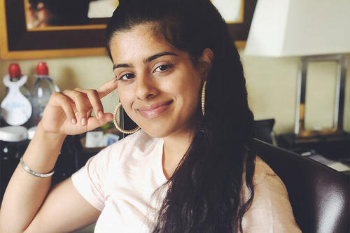 Gurtaran Johal, dark hair, white shirt, large hoop earrings, poses at home.