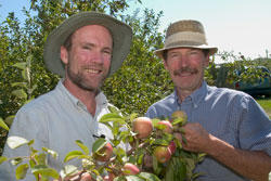 Jim Luby and David Bedford stand behind their apples
