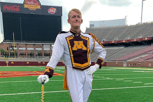 Chamberlain Gregg, in white drum major suit, poses dramatically on the football field.