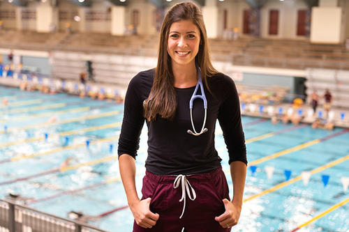 Chloe Portela stands in the U of M Aquatic Center with a stethoscope around her neck.
