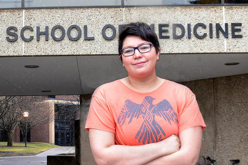 Goodsky, dark hair, dark glasses, with peach-colored T-shirt with phoenix graphic, stands, arms crossed, before a building labeled School of Medicine.