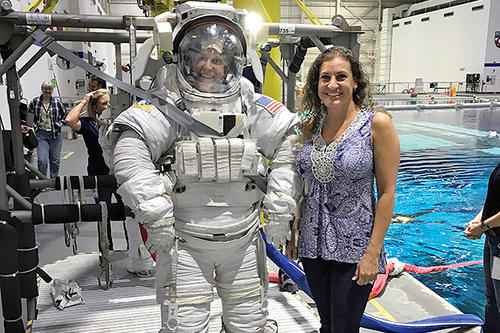 Heather McDonald stands next to person in spacesuit next to a pool.