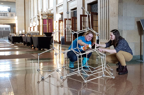 In a well-lit Northrop lobby, two female students construct a model of a diamond crystal.