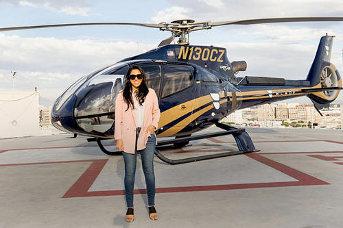 Law grad Shivani Parikh, long dark hair, sunglasses, white shirt, pink blazer, blue jeans, stands on a helipad in front of a helicopter. stands