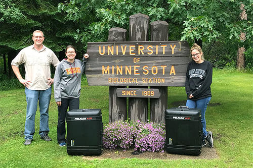 Peter Larsen, Kenwyn Shriner, and Laramie Lindsey alongside their mobile lab, which fits neatly into two suitcases.