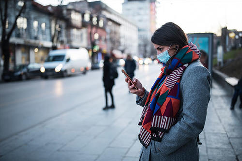 Woman on the street with face mask looking at her phone