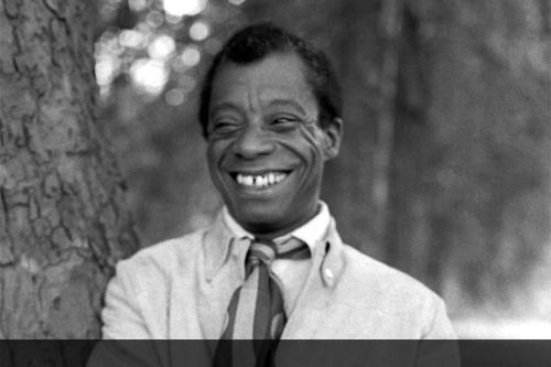 James Baldwin smiling and leaning on tree