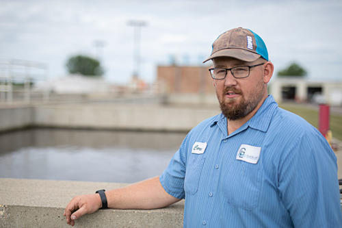 Corey Smith, with beard, glasses, blue shirt and cap, at Glacial Lakes Wastewater Treatment Facility, Spicer, Minnesota