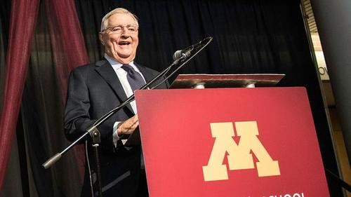 Former U.S. Vice President Walter Mondale smiles as he addresses a crowd at the University of Minnesota's Humphrey School of Public Affairs, standing behind a lecture with a large Maroon face highlighted by a Gold Block M