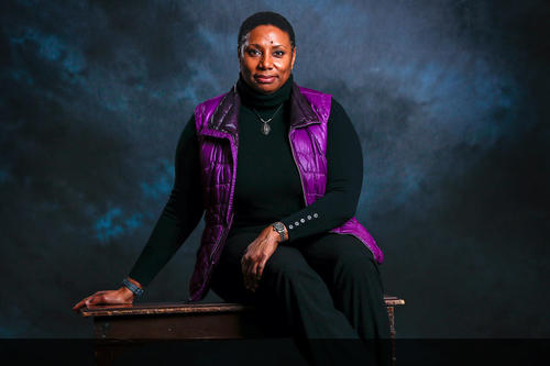 Rhonda Franklin wearing bright purple winter vest and black clothes in front of dark blue cloudy background