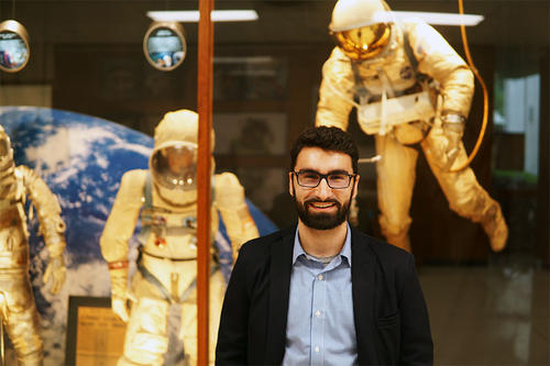 Simon Ozbek in front of spacesuits at NASA