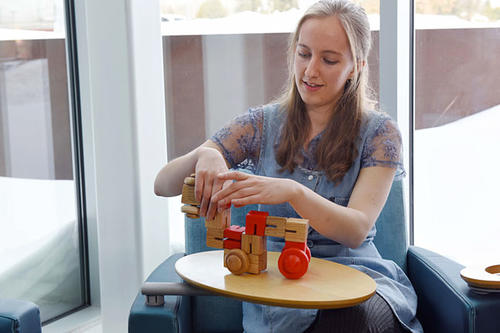Micki Grover playing with wooden toys she designed