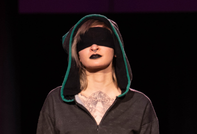 Model on runway wearing hood and black cloth over eyes